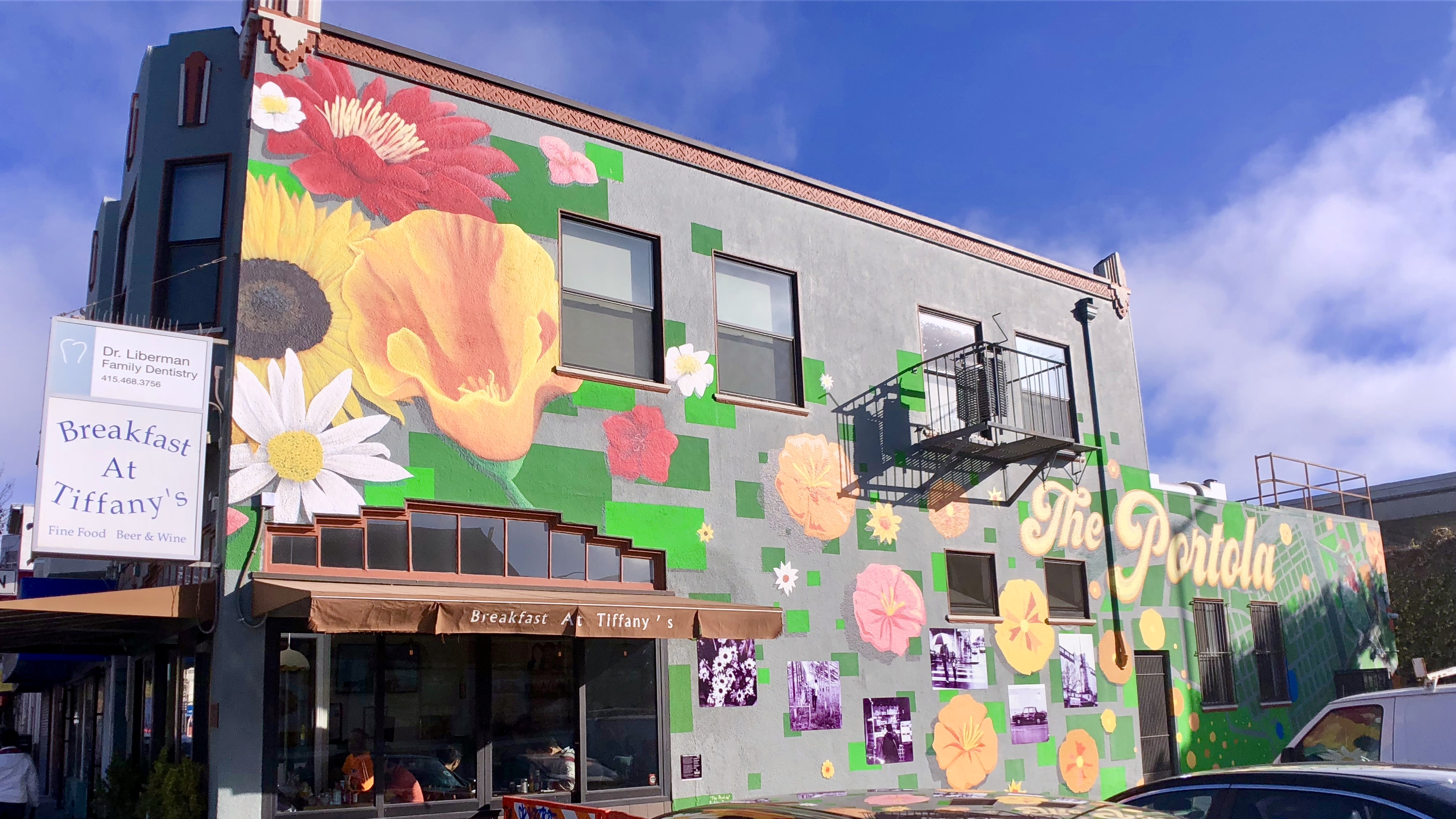 A colorful mural of flowers and abstract shapes on the side of a building.