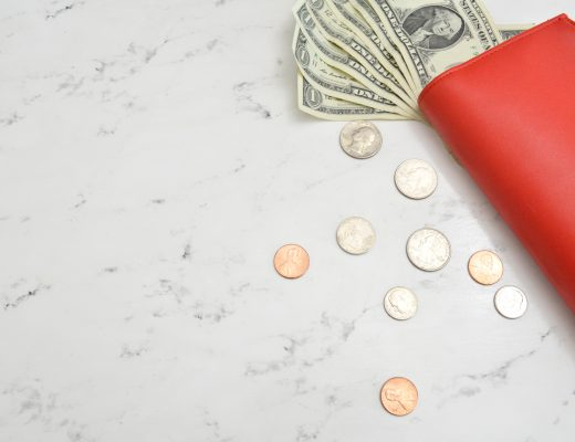 Red wallet with dollar bills and coins on marble surface